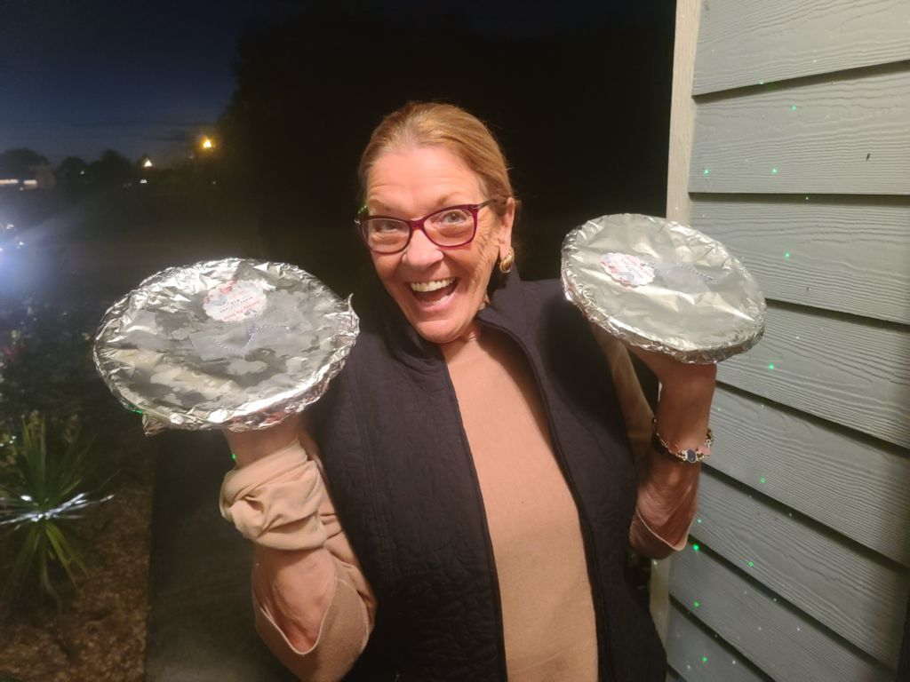 lady smiling while holding 2 pies