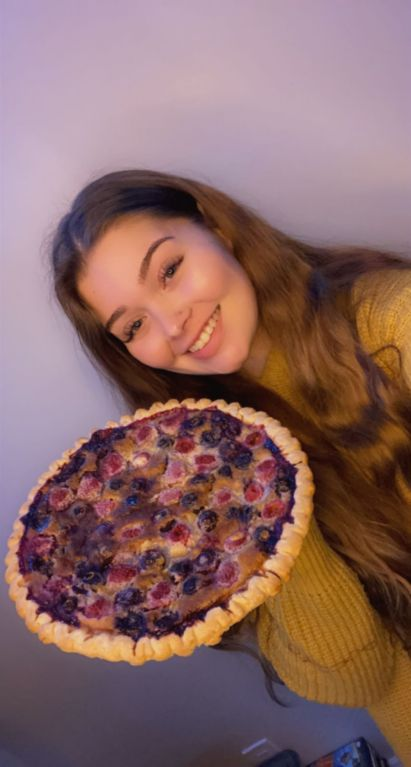 girl smiling while holding a pie